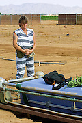 "05 JULY 2001 -- PHOENIX, AZ:  A member of the women chain gang in Maricopa County, Phoenix, AZ, stands at the head of a casket while they bury a homeless person in the county's ""Potter's Field"" or cemetery for the indigent. Maricopa county sheriff Joe Arpaio claims to have the only women's chain gang in the United States. He has been criticized for the chain gang but claims to be an ""equal opportunity incarcerator."" He has said that if puts men on a chain gang he will also put women on a chain gang. The women are prisoners in the county jail and volunteer for duty on the chain gang because it gets them out of the jail for six hours a day. The chain gang also buries the county's homeless and indigents. PHOTO BY JACK KURTZ"