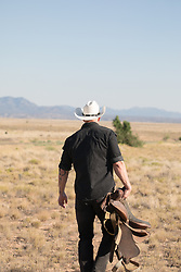 cowboy walking on a ranch with a saddle