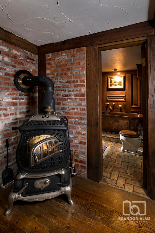 A old wood burning stove with a peek into an old vintage bathroom. Photo by Brandon Alms Photography