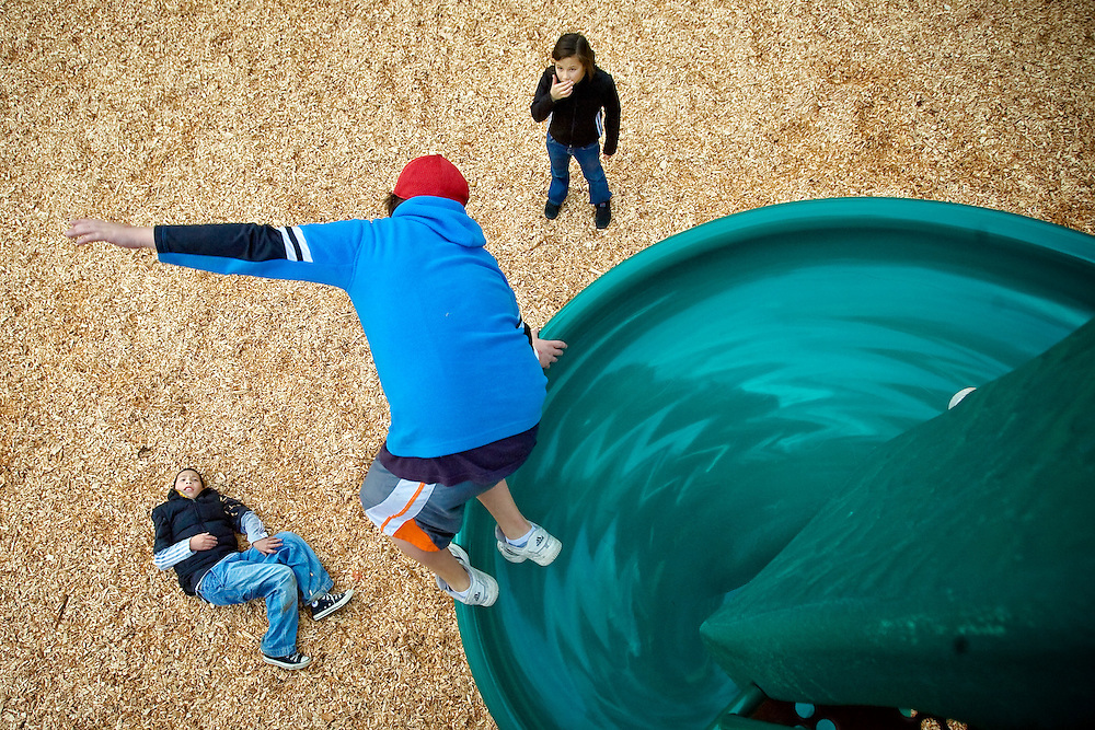 JEROME A. POLLOS/Press..Evan Puskash, left, and his siter Ember Puskash, watch as Kanyon Cooke jumps off the slide Friday at North Pines Park in Coeur d'Alene.