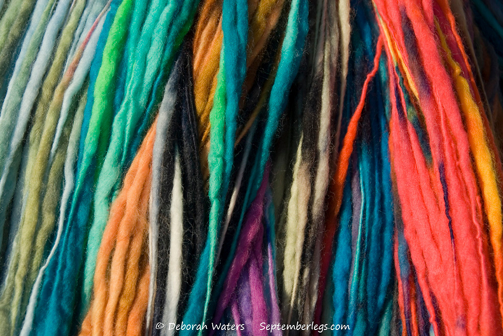 Close up on mixed colours of dyed wool hanging on a rail, for sale at the Green Gathering, Chepstow, Wales
