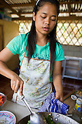 18 FEBRUARY 2008 -- BONG TI, KANCHANABURI, THAILAND: A girl makes dinner for other refugee children at the Bamboo School in Bong Ti, Thailand, about 40 miles from the provincial capital of Kanchanaburi. Sixty three children, most members of the Karen hilltribe, a persecuted ethnic minority in Burma, live at the school under the care of Catherine Riley-Bryan, whom the locals call MomoCat (Momo is the Karen hilltribe word for mother). She provides housing, food and medical care for the kids and helps them get enrolled in nearby Thai public schools. Her compound is about a half mile from the Thai-Burma border. She also helps nearby Karen refugee villages by digging water wells for them and providing medical care.  Photo by Jack Kurtz