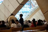 """È stata inaugurata il 1° luglio 2004, la nuova Chiesa di San Pio da Pietrelcina progettata dall'architetto Renzo Piano. Esattamente 45 anni prima, nel 1959,  veniva inaugurata la chiesa """"grande"""" di Santa Maria delle Grazie. .Sorta a fianco del santuario e convento in cui visse il frate, ha la forma di una conchiglia e la sua pianta ricorda quella della spriale archimedea. Enormi archi parto dal perimetro esterno e terminano nel fulcro della """"conchiglia"""" dove è posto l'altare. Possenti staffe d'acciaio, ancorate agli archi, sorreggono la volta che ricoperta di rame preossidato espone alla vista un intenso un colore verde-rame.   .Con i suoi 6000 mq, è la seconda chiesa più grande in Italia per dimensioni, dopo il Duomo di Milano. Può ospitare oltre 7000 persone e per la sua realizzazione sono state impiegati 30.000 metri cubi di calcestruzzo, 1.320 blocchi in pietra di Apricena, 70.000 metri cubi di scavo in roccia, 60.000 chili di acciaio, 500 mq di vetro, 19.500 mq di rame preossidato. Ogni anno è meta di oltre sei milioni di pellegrini..Nella foto la parte interna della chiesa con i suoi archi che si incrociano in un gioco di linee curve mentre è in corso una celebrazione eucaristica."""