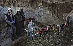 20010929-SARICHA, AFGHANISTAN: People pray at the grave of the famouse leader of Anti-Taliban Nothern Alliance Ahmad Shah Masood in Saricha, Saturday, 29 September, 2001. Ahmad Shah Masood was killed by explosion on September 09 caused by suicide bombers posing as Arab journalists.