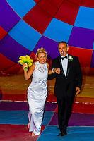 A just married couple pose inside an inflated balloon envelope, Albuquerque International Balloon Fiesta, Albuquerque, New Mexico USA.