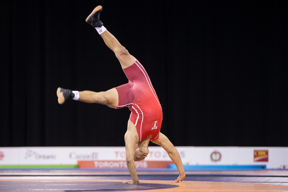 Mario Molina of Peru does a cartwheel following his win over Jefrin Mejia of Honduras in the bronze medal match for the  66kg class of the men's greco-roman wrestling at the 2015 Pan American Games in Toronto, Canada, July 15,  2015.  AFP PHOTO/GEOFF ROBINS