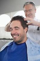 Barber preparing man for haircut in barber shop