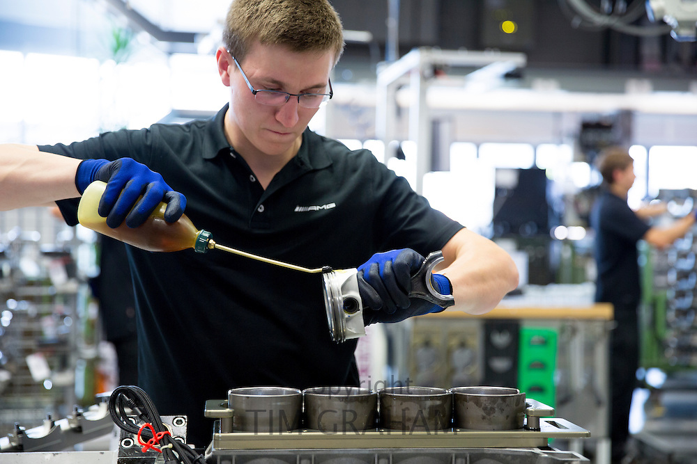 Mercedes-AMG engine production factory in Affalterbach, Germany - engineer applying lubricating oil to piston for 6.3 litre V8 engine