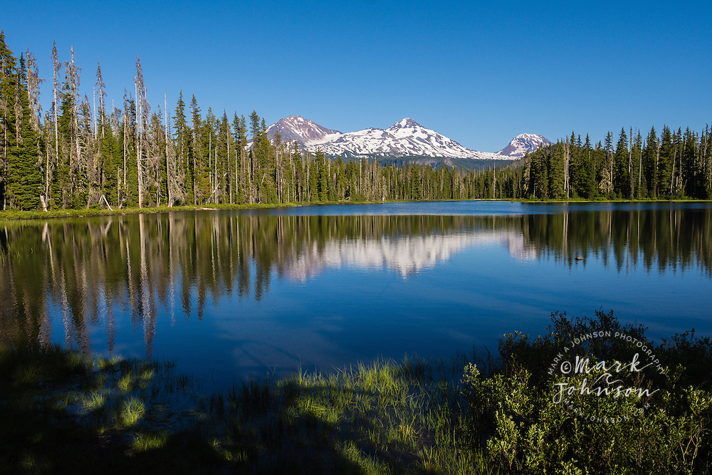 Snow Covered Mountains reflected in tranquil lake, Oregon, USA