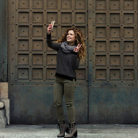 Young blonde woman taking a selfie in front of an ancient metal door