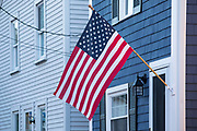 Patriotic Stars and Stripes flag at traditional clapboard home in Newport, Rhode Island, USA