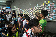 Protesters walk past a wall covered in protest notes beside of the Central Government Offices, during a protest against a proposed extradition law in Hong Kong, SAR China, on Wednesday, June 12, 2019. Hong Kong's legislative chief postponed the debate on legislation that would allow extraditions to China after thousands of protesters converged outside the chamber demanding the government to withdraw the bill. Photo by Suzanne Lee/PANOS