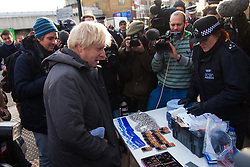 Ealing, London, December 9th 2014. Mayor of London Boris Johnson visits Ealing accompanied by Met Police Commissioner Sir Bernard Hogan-Howe hold a walkabout in Ealing to announce details of the historic deal secured for the New Scotland Yard site in Victoria. PICTURED: Mayor Boris Johnson talks with police officers at a cycling safety stand outside Ealing Broadway station.
