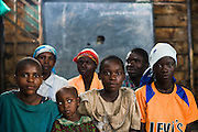 Maombi, 15, (right) and her family in the classroom where they live at the Angalisho adventist primary school in Goma, Eastern DRC, on Sunday December 14, 2008. Maombi and her family found shelter the school when they arrived in Goma after conflict forced them out of their home in Burumba, 12km from Goma. Every morning, they vacate the classroom to allow children to attend school, and come back in the afternoon. they've lived here for five weeks.