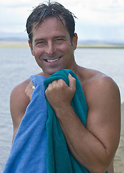 Portrait of smiling man holding towels in his hands by a lake in New Mexico