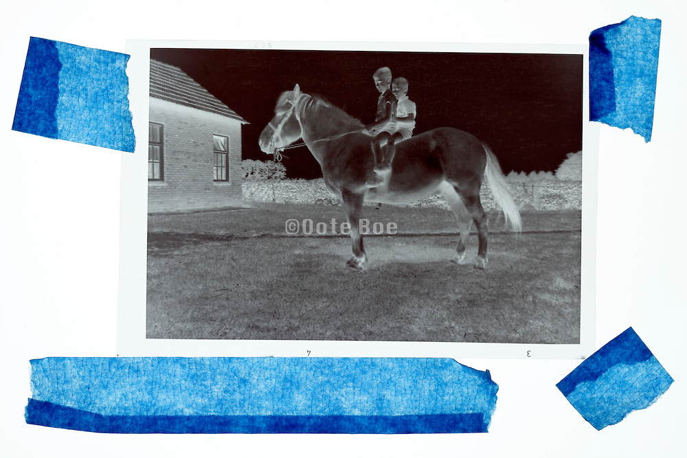 black and white negative film photograph of two little children sitting on a horse