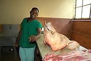 Dunkelh?utiger Verk?ufer posiert in der Markthalle  der kubanischen Metropole Havanna mit Zigarre vor einem Schweinekopf