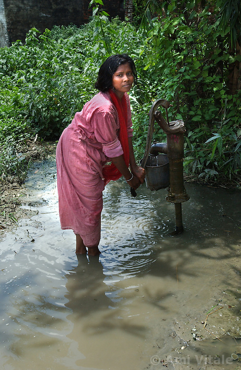 """BIHAR, INDIA: AUGUST 14: Lalita'gathers water at a pump in her village of Koprah,  60 kilometers from Sitamarhi in northern Bihar, India August 14, 2003. She was visiting after an eight month training course at a MSK and 4 months of teaching karate in another district in Bihar. She has overcome great barriers in a society that regards her as the most disadvantaged since she is a female in one of  the lowest castes in India, the """"Musahar """"caste which means rat eaters. This tenacious young woman attended,  Mahila Shikshan Kendra, a Women's Education Center,  depsite her father's protests and learned how to read, write and defend herself in a community which frequently abuses women. Now she is teaching karate to other young women in a MSK in Amos block. Bihar is the poorest state in India and women suffer  greatly because of the poverty, lack of education and opportunities. Most of the girls who are attending the eight month course have had to overcome tremendous resistance from families and a society entrenched in the  weight of a caste system which discourages those from the lower castes to be educated, especially women. The 10 centers with 40 students in each are being funded by the World Bank although it was initially started by Unicef . .(Ami Vitale)"""