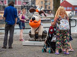 "© Licensed to London News Pictures.  01/07/2018; Bristol, UK. Gromit Unleashed 2. People look at the  ""Honeydew"" Gromit character installed at Bristol Harbourside for the Gromit Unleashed 2 sculpture trail. Gromit Unleashed 2 will see the Academy Award®-winning character Gromit by Nick Park at Aardman Animations returning to Bristol in 2018 for the second time on sculpture trails to raise money for  the Grand Appeal charity. The character of Gromit will be joined by Wallace and their arch nemesis Feathers McGraw. The trail will feature over 60 giant sculptures designed by high-profile artists, designers, innovators and local talent. Sculptures will be positioned in high footfall and iconic locations around Bristol and the surrounding area. Photo credit: Simon Chapman/LNP"