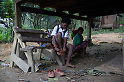 Phong, 12, puts his socks on before leaving on a 30 minute walk simply to get to the edge of the forest. After that he must sit on a motorbike for a further 15 minutes just to get to school. Because of the distance and difficulty for the parents the children often miss school.<br /> <br /> The Maniq of Trang province differ slightly as they were the first to give up nomadic life and became permanently settled in their own remote forest village.<br /> <br /> Evidence suggests that the Maniq, a Negrito tribe of hunters and gatherers, have inhabited the Malay Peninsula for around 25,000 years. Today a population of approximately 350 maniq remain, marooned on a forest covered mountain range in Southern Thailand. Whilst some have left their traditional life forming small villages, the majority still live the way they have for millennia, moving around the forest following food sources. <br /> <br /> Quiet and reclusive they are little known even in Thailand itself but due to rapid deforestation they are finding it harder to survive on the forest alone and are slowly being forced to move to its peripheries closer to Thai communities.