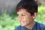 Smiling young boy outside with copy space to right