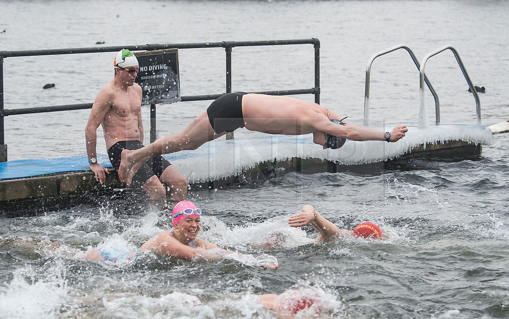 © Licensed to London News Pictures. 03/03/2018. London, UK. Members of the Serpentine Swimming Club brave freezing overnight temperatures as they enjoy an early morning swimming race at sunrise in the Serpentine in Hyde Park, London. Large parts of the UK are recovering from a week of sub zero temperatures and heavy snowfall, following two severe cold fronts. Photo credit: Ben Cawthra/LNP