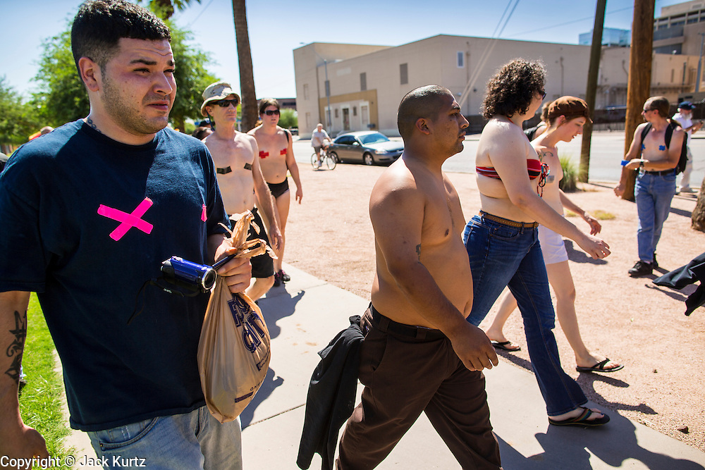 26 MARCH 2012 - PHOENIX, AZ:  About 40 people marched through central Phoenix Sunday to call for a constitutional amendment to give women the same right to go shirtless in public that men have. The Phoenix demonstration was a part of a national Topless Day of Protest. Phoenix prohibits women from going topless in public so protesters, women and men, covered their nipples and areolas with tape. The men did it to show solidarity with the women marchers.   PHOTO BY JACK KURTZ