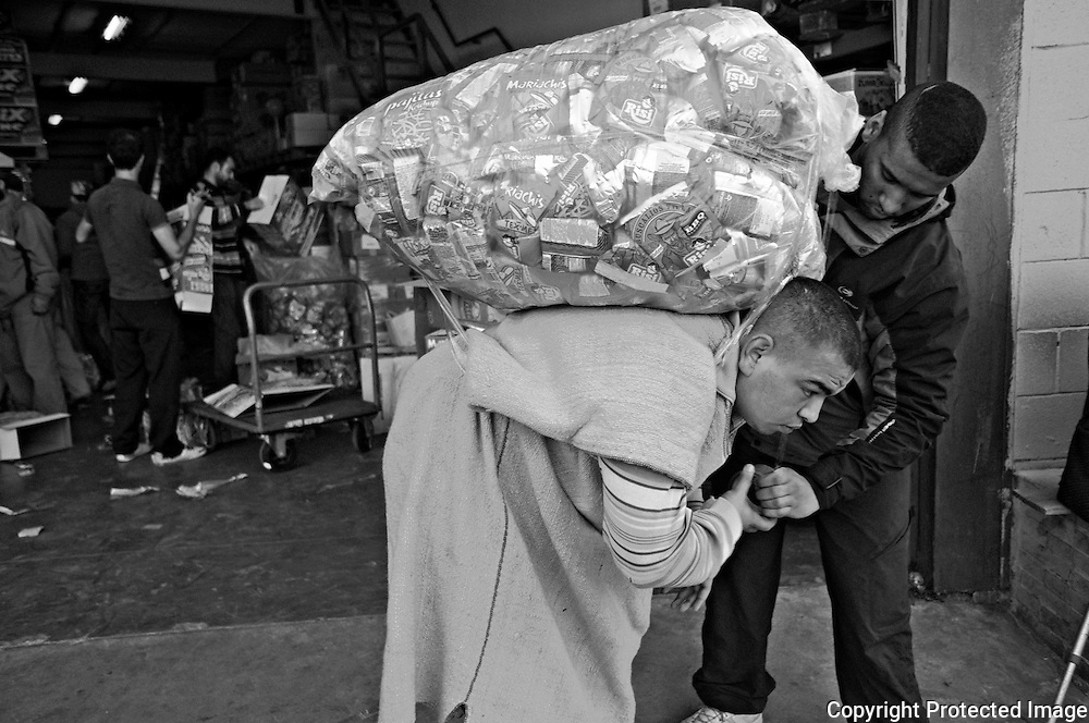 CEUTA, SPAIN - JUNE 27, 2010 :A man with adhesive tape insure the goods  to  a carrier at the warehouses located around the pedestrian cross border ofl Biutz. Thousands  of people are involved in transporting smuggled goods from Ceuta (an Spanish enclave on the North African coast) to Morocco, it is estimated that every day enter 10.000 porters, mostly women, that it make between three and five trips to Morocco with all types of products purchased on  the warehouse border area of  Biutz in Ceuta, Spain .( Photo by Jordi Cami  )