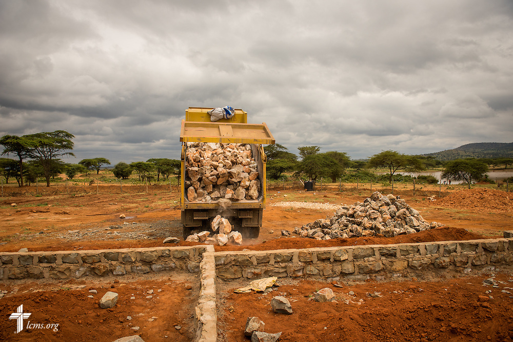 A dump truck offloads raw materials for the construction of the Lenkishon ELCK (Evangelical Lutheran Church in Kenya) Project 24 site on Saturday, June 25, 2016, in Lenkishon, Kenya.  LCMS Communications/Erik M. Lunsford