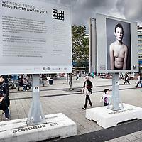 Nederland, Amsterdam , 5 september 2011..Allochtone voorbijgangers op het Osdorpplein bekijken de Billboards met foto's van de Pride Photo Award 2011-1, een jaarlijks terugkerende Internationale fotowedstrijd over seksuele en gender diversiteit. De foto's laten zien hoe divers de lesbische, homoseksuele, biseksuele en transgender gemeenschap (LHBT) is en dat er evenveel vormen zijn van mannelijkheid en vrouwelijkheid als er mensen zijn..Foto:Jean-Pierre Jans