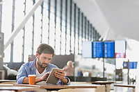 Man using digital tablet while waiting for his flight in airport