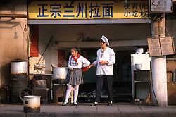 CHINA SHANGHAI MAY99 - A Chinese woman accompanies her daughter, dressed in a school uniform, from her street restaurant in Old Shanghai.  jre/Photo by Jiri Rezac
