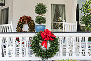 A porch railing of the Meeting Street Inn decorated with a Christmas wreath on Meeting Street in Charleston, SC.