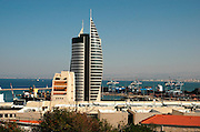 High rise modern building in Downtown Haifa, Israel. The Haifa port is in the background
