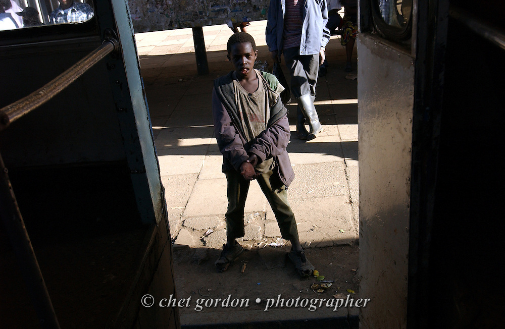A young street boy begs for change at a bus stop in downtown Nairobi, Kenya in November 2002.