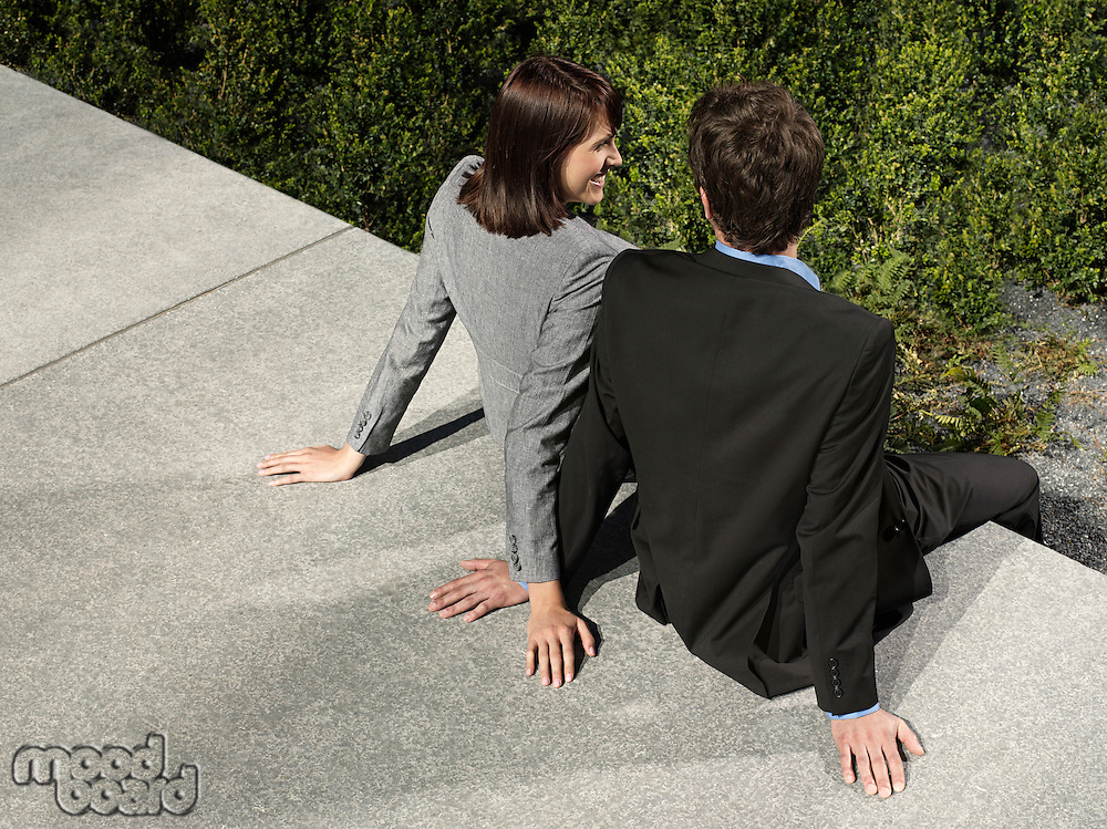 Business man and woman sitting on wall outdoors back view
