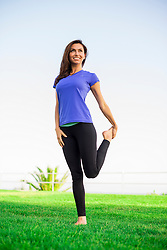 Woman Standing on Grass Stretching her Leg