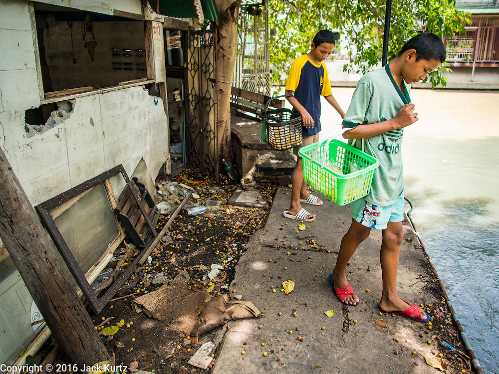 09 SEPTEMBER 2016 - BANGKOK, THAILAND:  Boys selling fruit walk past one of the 15 homes torn down in the Pom Mahakan community slum over the weekend. Forty-four families still live in the Pom Mahakan Fort community. The city of Bangkok has given them provisional permission to stay, but city officials say the permission could be rescinded and the city go ahead with the evictions. The residents of the historic fort have barricaded most of the gates into the fort and are joined every day by community activists from around Bangkok who support their efforts to stay.           PHOTO BY JACK KURTZ