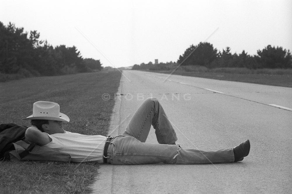 cowboy taking a break to rest on an empty road
