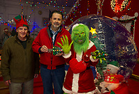 """Tinsel"" Ernie Bolduc and Mayor Ed Engler present the key to Christmas Village to Mayor Grinch on opening night Thursday evening.  (Karen Bobotas/for the Laconia Daily Sun)"