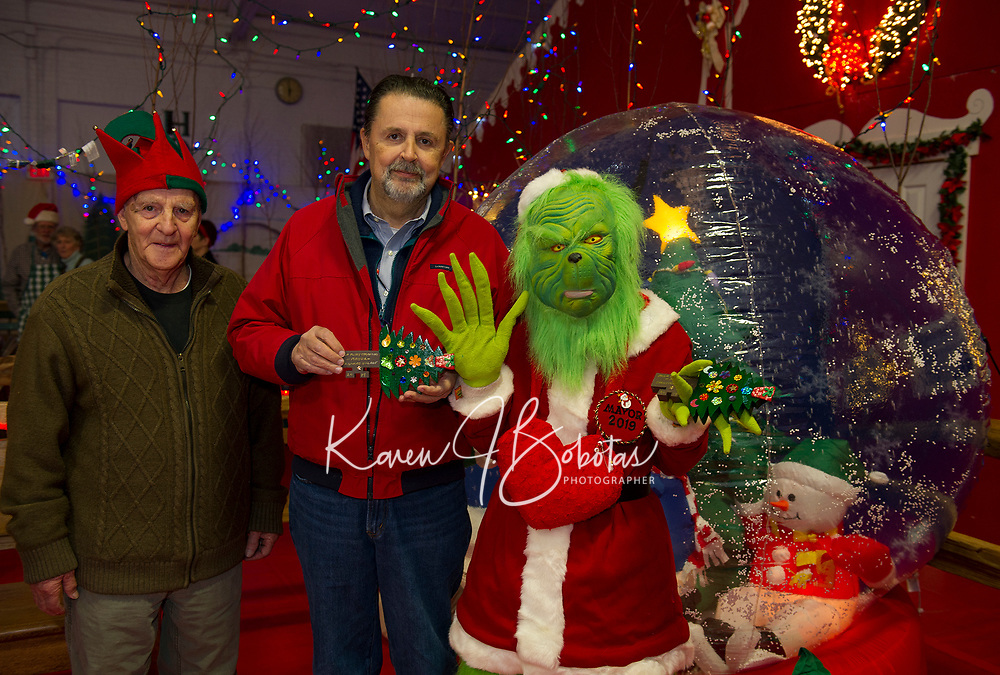"""""""Tinsel"""" Ernie Bolduc and Mayor Ed Engler present the key to Christmas Village to Mayor Grinch on opening night Thursday evening.  (Karen Bobotas/for the Laconia Daily Sun)"""