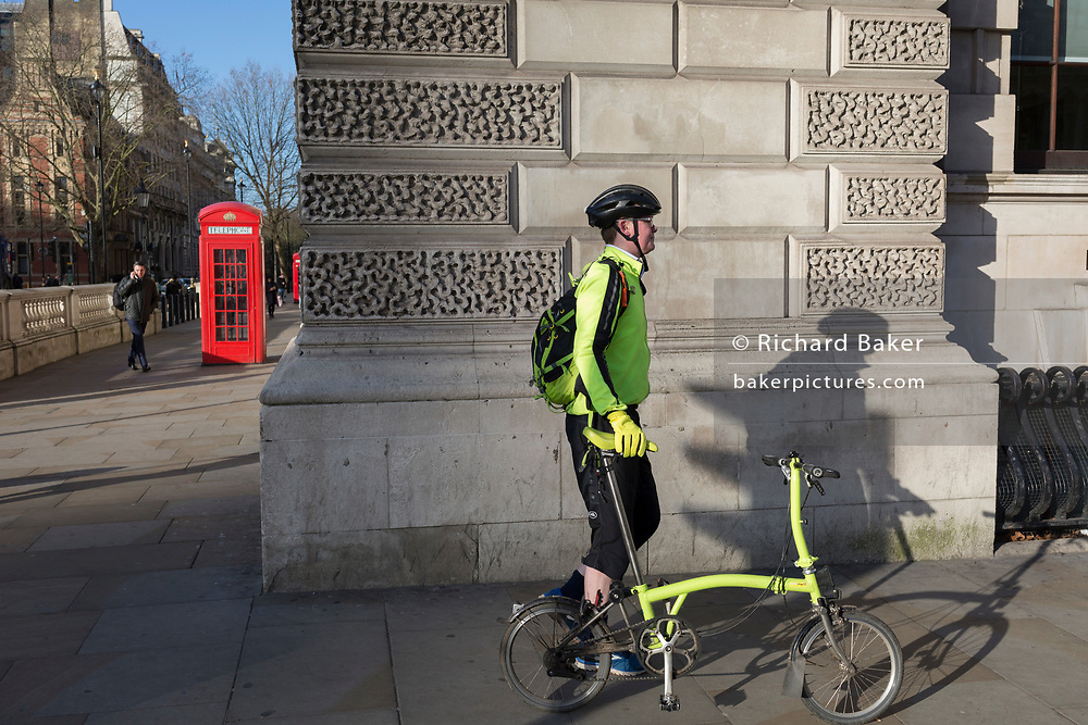 A commuter walks his fold-up bike in the direction of Whitehall, on the corner of Parliament Street and Parliament Square, Westminster, on 29th January 2020, in London, England.
