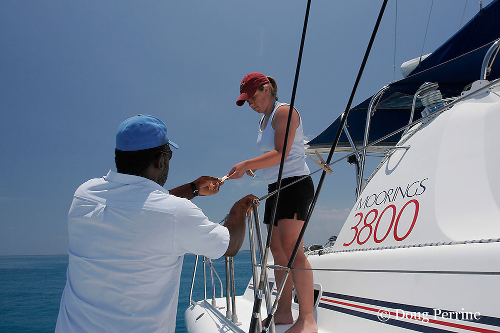 Friends of Nature ranger Tamba Nicholas sells an entry ticket to a visitor on a chartered yacht in the Gladden Spit & Silk Cayes Marine Reserve, off Placencia, Belize, Central America ( Caribbean Sea )