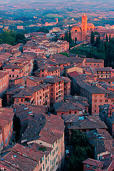 Europe, Italy, Tuscany, Siena, historic stone houses with Cathedral in distance, viewed from above