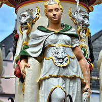 Fountain in Market Square in Trier, Germany<br /> In the center of the market square in the old town of Trier, Germany, is a Renaissance water fountain with four allegorical sculptures.  This statue with the broken column represents fortitude.  The other three (off camera) symbolize justice, temperance and prudence.