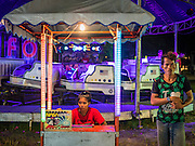 "15 JUNE 2105 - NARATHIWAT, NARATHIWAT, THAILAND:  ""Carneys"" wait for people to ride their attraction at a fair in Narathiwat to celebrate 100 years of Narathiwat. The city has been a Muslim city for centuries, but when Siam (now Thailand) annexed the three southern provinces they changed the name to Narathiwat.     PHOTO BY JACK KURTZ"