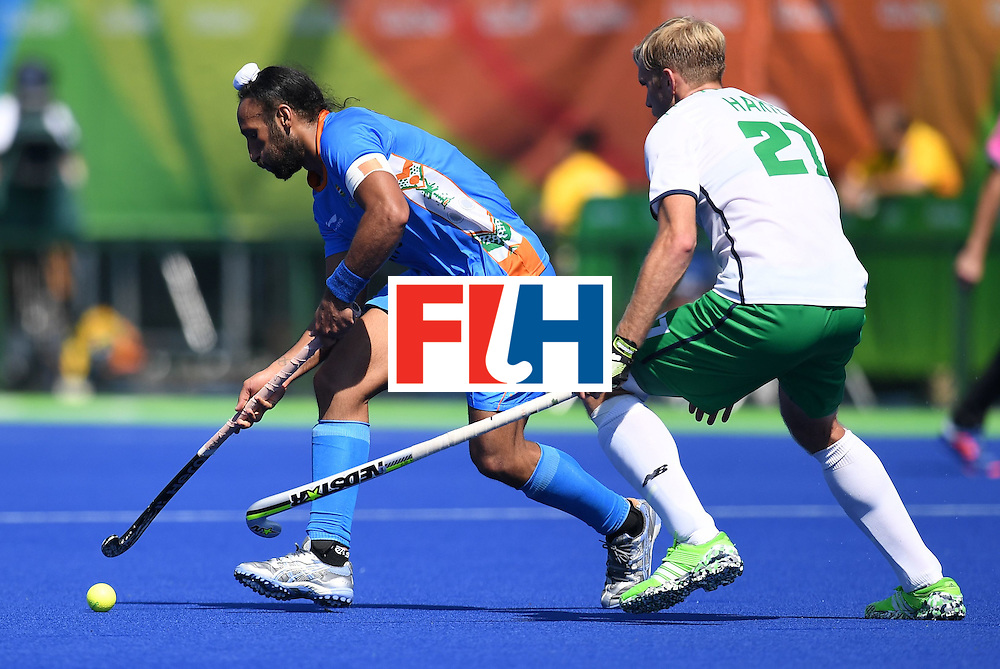 India's Sardar Singh (L) fights for the ball with Ireland's Timothy Cockram during the men's field hockey India vs Ireland match of the Rio 2016 Olympics Games at the Olympic Hockey Centre in Rio de Janeiro on August, 6 2016. / AFP / MANAN VATSYAYANA        (Photo credit should read MANAN VATSYAYANA/AFP/Getty Images)