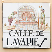 Ceramic street sign in Madrid, Spain Calle de Lavapies - feet washing street