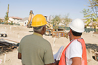 Surveyor and contraction worker at construction site, back view