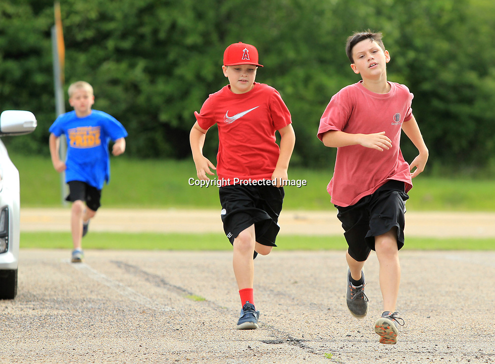 """Tatum Blankenship, 9, his brother Turner, 10, and Emil Anderson, 10, run their 400 meters on Memorial Day morning at the CrossFit gym in Tupelo. The children took part in the Memorial Day Murph Challenge which they called the """"Little Murph"""", that includes 50 pull-ups, 100 sit-ups, 200 air squats and a 400 meter run. The Murph is a workout in the honor of fallen Navy Lieutenant Michael Murphy."""
